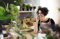 Happy young woman on the phone in a small shop with plants - HAPF03013