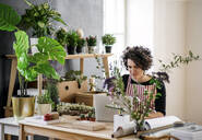 Young woman using laptop in a small shop with plants - HAPF03016
