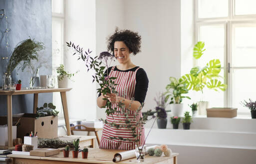 Happy young woman arranging flowers in a small shop - HAPF03025