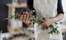 Close-up of woman holding flowers in a small shop - HAPF03028