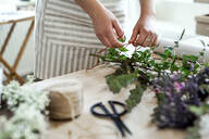 Close-up of woman arranging flowers in a small shop - HAPF03046