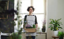 Happy young woman holding flowers in a cardboard box in a small shop - HAPF03052