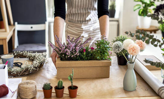 Close-up of woman with flowers inside a cardboard box on table - HAPF03055