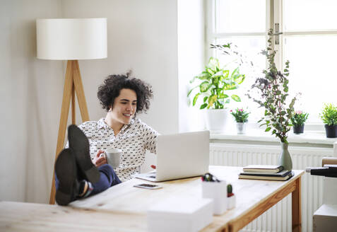 Relaxed young woman working on laptop at desk - HAPF03064