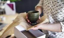 Close-up of woman wrapping an earthenware mug - HAPF03073