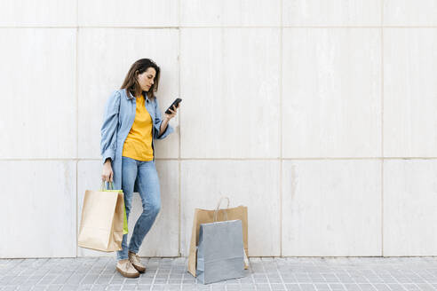 Young brunette woman using smartphone after shopping - JRFF03794