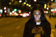 Young woman using smartphone in the city at night - JRFF03821