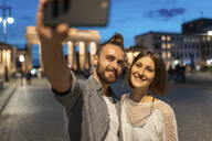 Happy couple taking a selfie at Brandenburg gate at blue hour, Berlin, Germany - WPEF02134