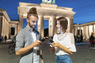 Happy couple using smartphones at Brandenburg gate at blue hour, Berlin, Germany - WPEF02137