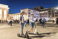 Young couple with electric scooters at Brandenburg Gate at night, Berlin, Germany - WPEF02143
