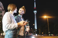 happy couple using smartphones in the city at night, Fernsehturm in the background, Berlin, Germany - WPEF02146