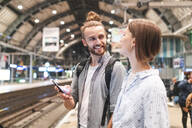 Young couple waiting for the train at the station and using smartphone, Berlin, Germany - WPEF02155