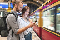 Young couple waiting for the train at the station and using smartphone, Berlin, Germany - WPEF02158
