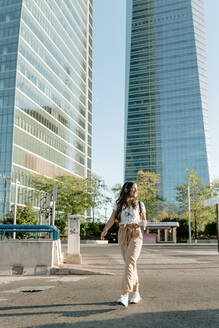 Young woman with take away drink crossing road, high-rise buildings in the background - KIJF02667