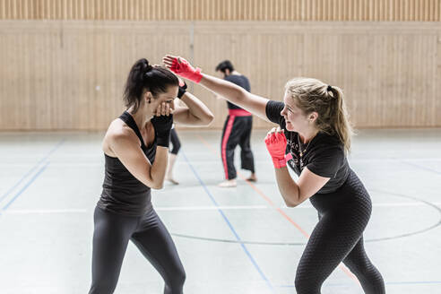 Female boxers practising in sports hall - STBF00454