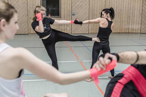 Female kickboxers practising in sports hall - STBF00457