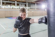 Smiling female boxer practising at punchbag in sports hall - STBF00460
