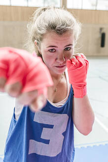 Portrait of confident female boxer in sports hall - STBF00475