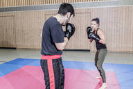 Female boxer sparring with coach in sports hall - STBF00478