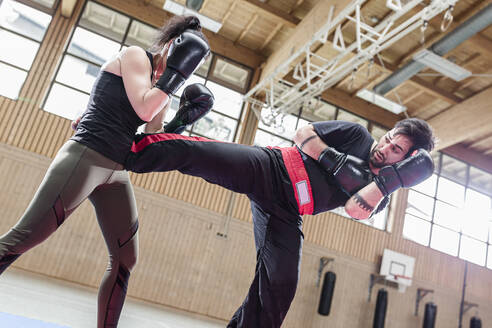 Female kickboxer sparring with coach in sports hall - STBF00481