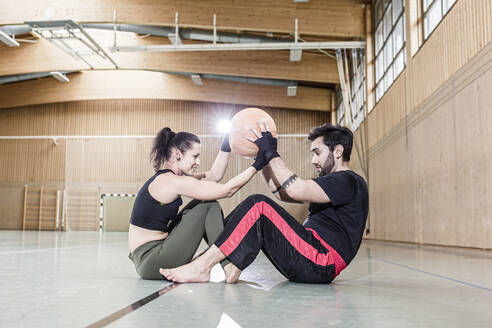 Man and woman practising with medicine ball in sports hall - STBF00487