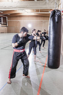 Coach and female boxers practising at punchbag in sports hall - STBF00496
