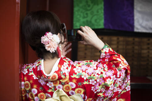 Japanese woman with traditional Japanese clothes taking a picture in Tokyo, Japan - ABZF02654