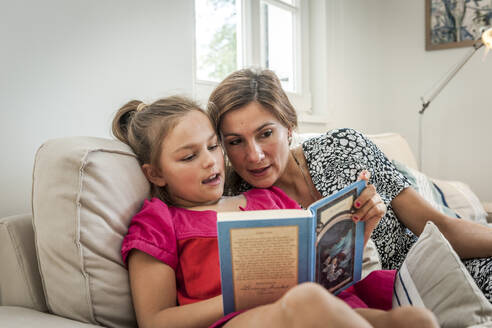 Mother reading book with daughter on couch in living room - EGBF00368