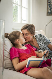 Mother kissing daughter with book on couch in living room - EGBF00371