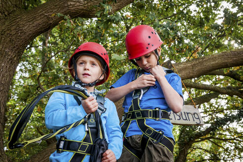 Boy and girl on a high rope course in forest - EGBF00401
