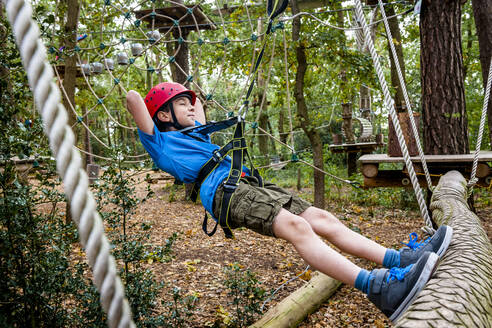 Relaxed boy on a rope course in forest - EGBF00407