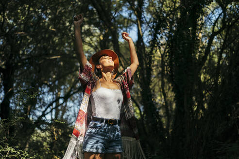Young curly haired woman wearing a brown hat, colorful shirt and white top with closed eyes and arms up feeling the sun in a dark forest. Vitoria, Spain - MTBF00050