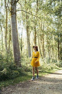 Young curly haired and blue eyes woman wearing brown hat, yellow dress and black sneakers looking up while is walking along a road in a forest - MTBF00053