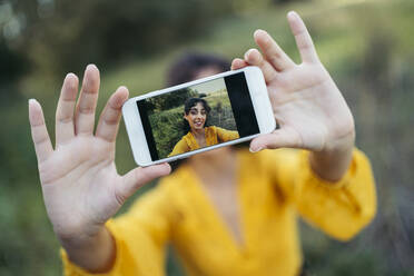 Happy young woman wearing yellow dress taking a white smartphone in front of her face and taking a selfie - MTBF00056