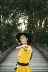 Young woman wearing a black hat and yellow dress with an analog camera shake hand to a camera on wooden boardwalk - MTBF00059