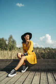 Young woman wearing a black hat and yellow dress with an analog camera sitting on wooden boardwalk - MTBF00062