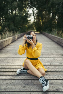 Young curly haired woman photographer wearing yellow dress and black sneakers taking a photo with an analog camera while is sitting in the floor of a wood bridge with forest in background - MTBF00065