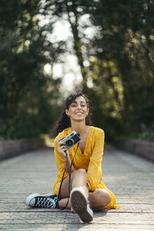 Happy young curly haired woman photographer wearing yellow dress and black sneakers holding an analog camera while is sitting in the floor of a wood bridge with forest in background. Vitoria, Spain - MTBF00068