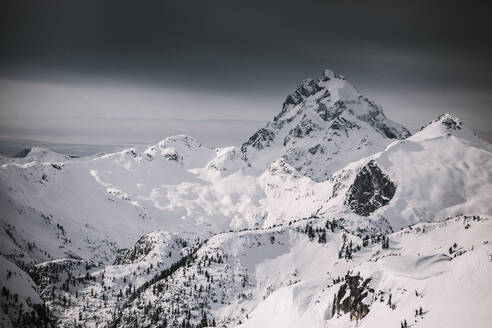 Winter storm approaches a snow covered peak. - CAVF65935