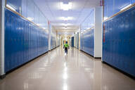 Rear view of boy running in school corridor - CAVF66473