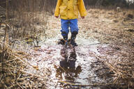 Low section of boy standing in dirty puddle - CAVF66476