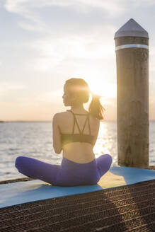 Rear view of woman meditating by sea against sky during sunset - CAVF66614
