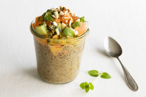 Jar of vegan pudding with chia, almond milk, persimmon, kiwi fruit, papaya, passion fruit and almonds - EVGF03530