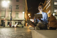 Portrait of happy young woman with digital tablet in the city by night, Lisbon, Portugal - UUF19130