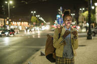 Portrait of young woman using earphones and smartphone in the city by night, Lisbon, Portugal - UUF19151