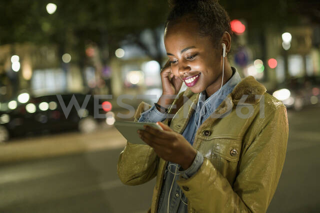 Portrait of smiling young woman using earphones and smartphone in the city by night, Lisbon, Portugal - UUF19154 - Uwe Umstätter/Westend61