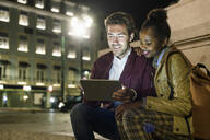 Portrait of smiling young couple using digital tablet in the city by night, Lisbon, Portugal - UUF19160