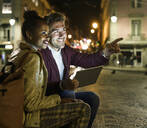 Portrait of smiling young couple with digital tablet in the city by night watching something, Lisbon, Portugal - UUF19163