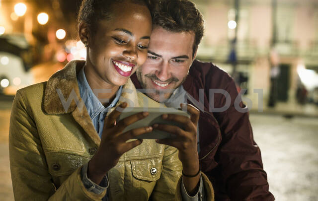 Portrait of happy young couple looking together at smartphone by night, Lisbon, Portugal - UUF19166 - Uwe Umstätter/Westend61