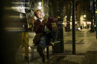 Portrait of laughing young man sitting at bus stop by night using smartphone, Lisbon, Portugal - UUF19175